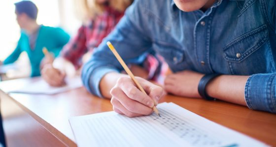 Students filling out answer sheets at exam